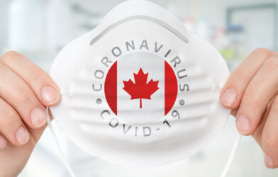 Person holding mask with Canadian flag for coronavirus / covid-19