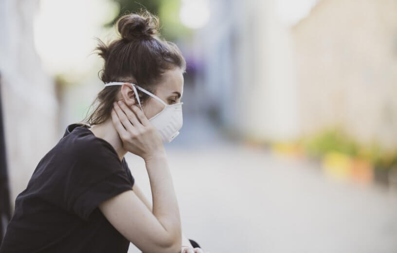 Loneliness during coronavirus outbreak: woman in mask feeling sad