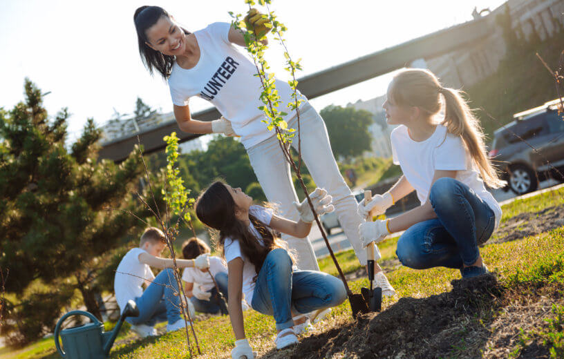 Woman volunteering to plant trees with children, helping environment