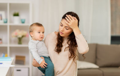 Exhausted, stressed mother with baby sighing