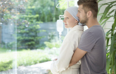 Man hugging sick girlfriend or wife with breast cancer during treatment