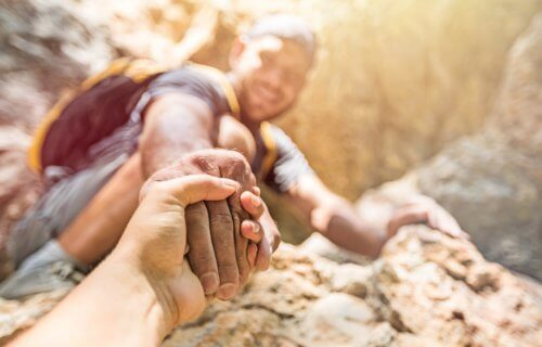 Good Samaritan: Man offers helping hand to another while rock climbing