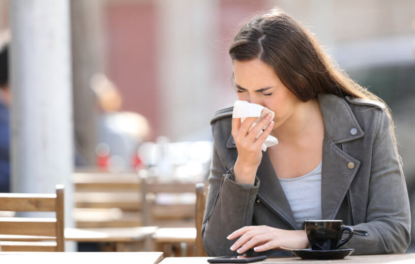 Sick woman blowing her nose, sneezing