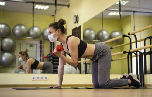 Woman wearing mask while working out at gym