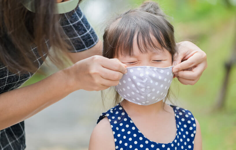 Mother putting a cloth mask on her child during the COVID-19 / coronavirus pandemic