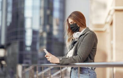 Woman wearing face mask while texting on phone during COVID-19 / coronavirus outbreak