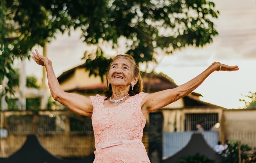 Long, happy life: Elderly woman with hands in the air