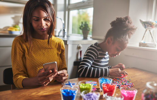 Mother looking at smartphone while playing with daughter