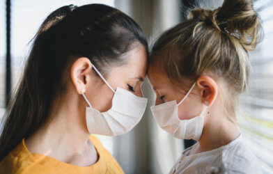 Mother, daughter wearing masks during coronavirus / COVID-19 outbreak, sad or grieving