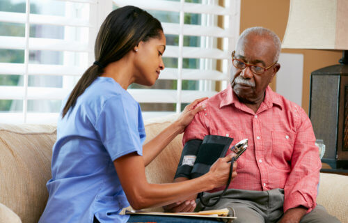 Nurse measuring older African American man's blood pressure