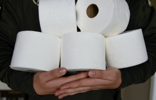 Person holding toilet paper stockpile
