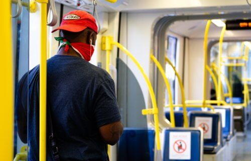 Man wearing a bandana or neck gaiter on train as face covering