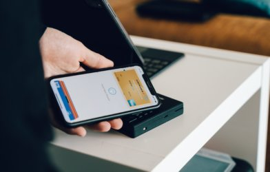 Person using credit cards on Apple Pay to purchase item while shopping
