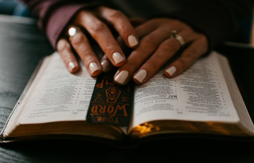 Woman's hands atop the Bible