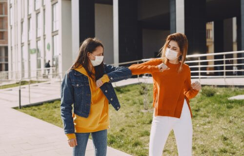 Women in masks elbow-bumping and social distancing during coronavirus pandemic