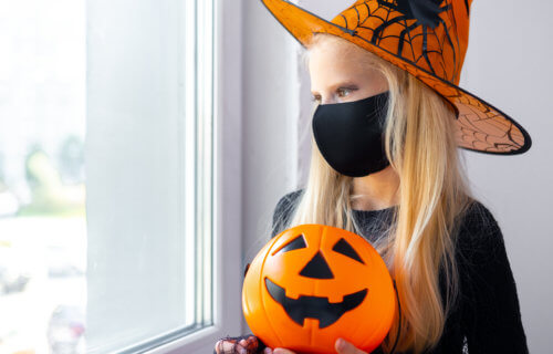 Young girl in face mask staying home for Halloween due to coronavirus / COVID-19