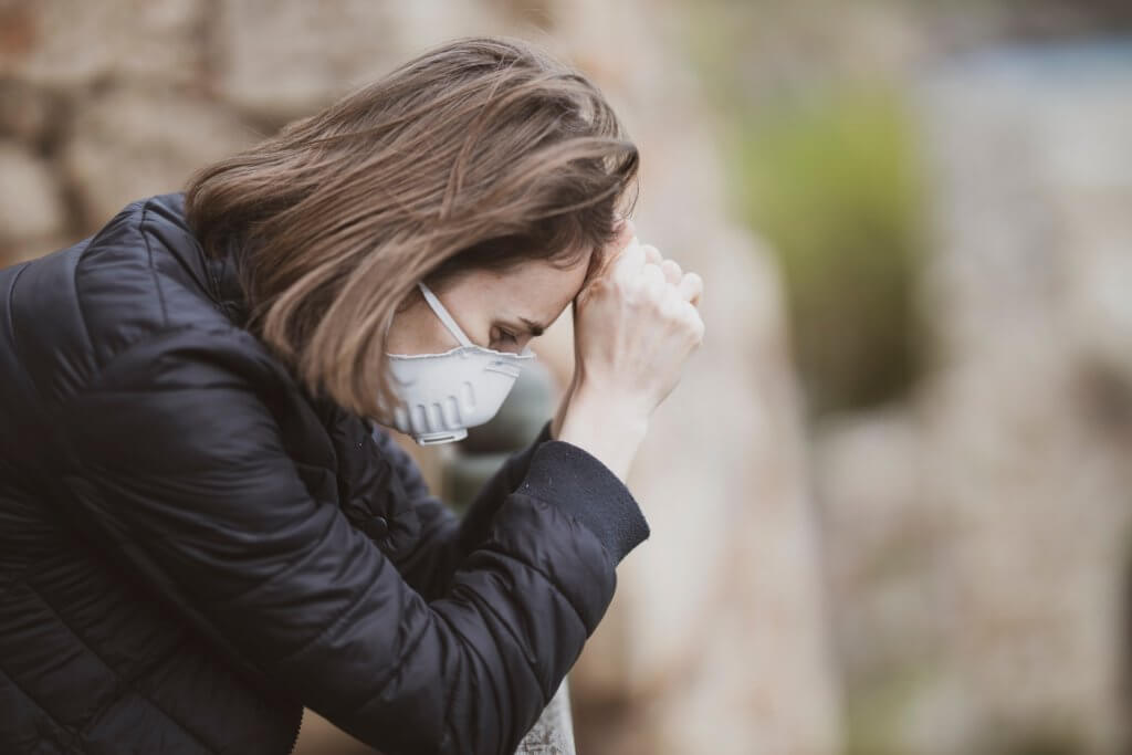 Sad, stressed woman wearing face mask during coronavirus outbreak