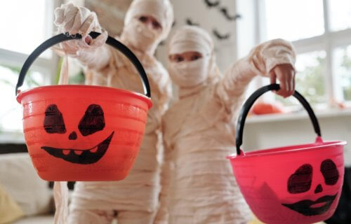 Children in Halloween mummy costumes with trick-or-treat candy buckets