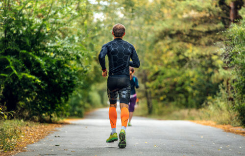 Man wearing compression socks and clothes running down road