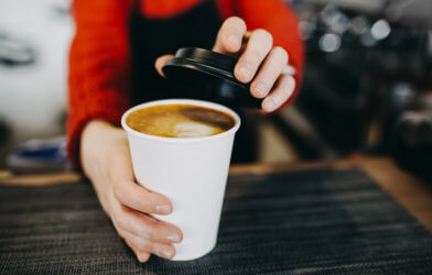 Barista holding coffee in paper cup