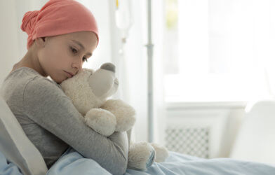 Young girl with cancer hugging teddy bear