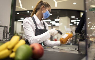 Grocery store cashier wearing face mask during coronavirus pandemic
