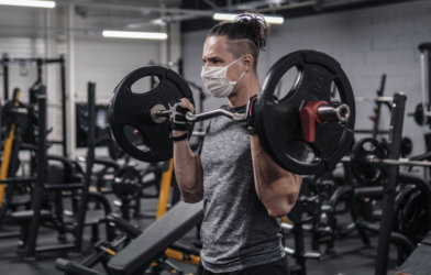 Man working out at gym with face mask on during COVID pandemic