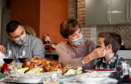 Family wearing face masks during Thanksgiving holiday dinner