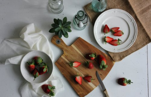 Plate of sliced strawberries on table with tablecloth