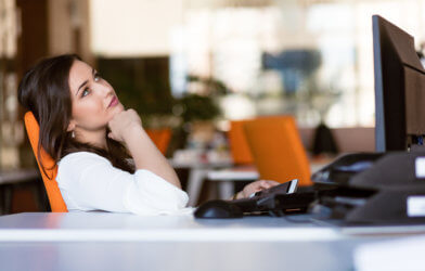 Woman sitting at office desk, daydreaming while working