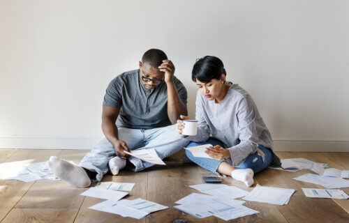 Couple sitting in pile of bills, as financial struggles, money worries, debt grow