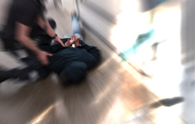 Police officer restraining suspect resisting arrest, placed in handcuffs