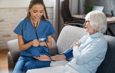 Nurse takes elderly patient's blood pressure