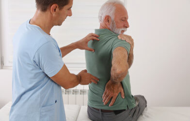 Older man battling shoulder pain, back pain, arthritis