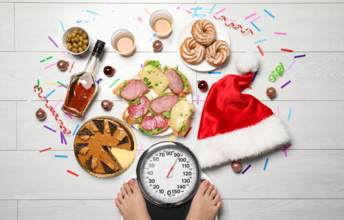 Holiday weight gain: Christmas food, sweets surrounding person weighing themselves on a scale