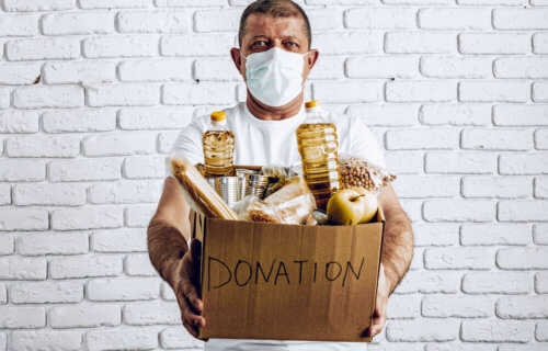Man holding donation box of food during COVID pandemic