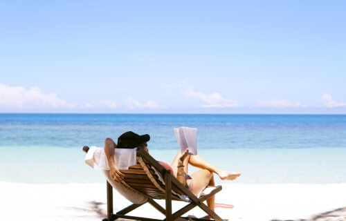 Woman reading a book on the beach, enjoying vacation