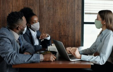 People wearing surgical face masks during meeting