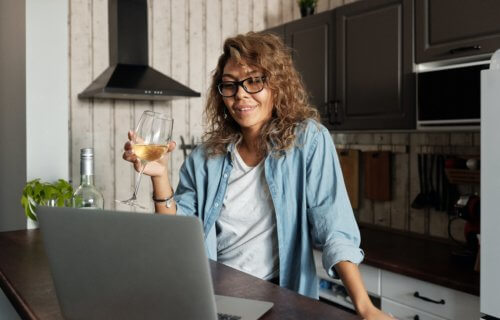 Woman drinking glass of wine on video chat with computer