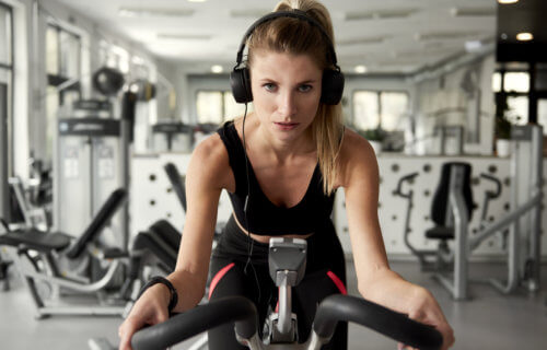 Woman working out on an exercise bike while listening to music
