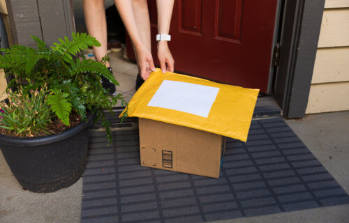 Person picking up packages from front door