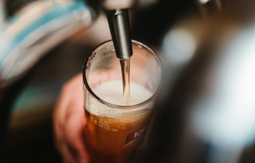 Beer being poured into glass from tap