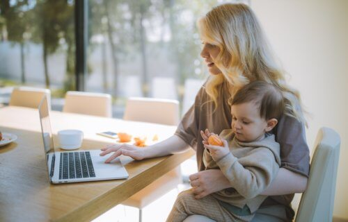 Mother holding child on lap while doing work on laptop