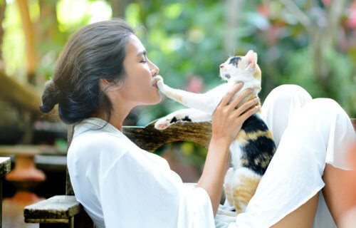 Woman playing with pet cat
