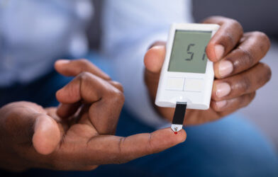 Man With Diabetes Checking Blood Sugar Level With Glucometer