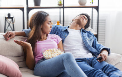 Girlfriend or wife upset with bored partner watching a movie