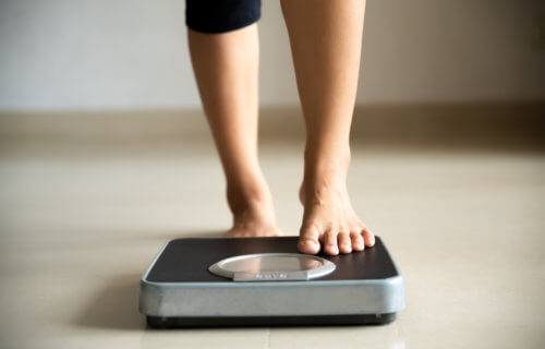 Woman stepping on scale, checking weight loss or weight gain