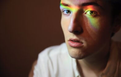 Gay man with rainbow over face for LGBTQ rights