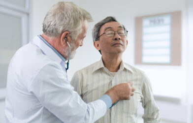 Doctor listening to middle-age patient's heartbeat