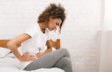 Woman in bed with stomach pain, cramps